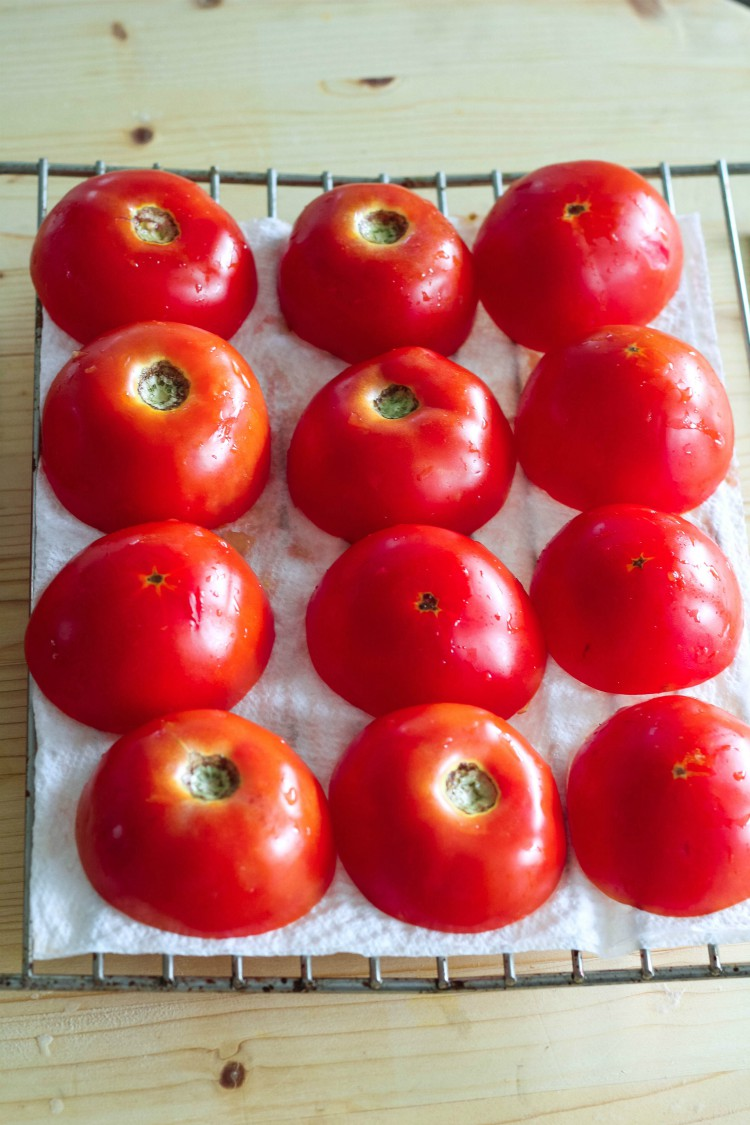 overhead image of tomatoes draining on paper towel lined rack