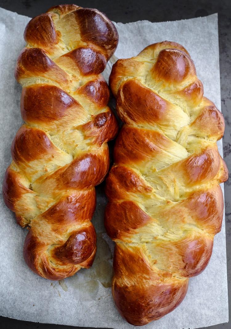 overhead image of sourdough discard challah loaves on baking sheet