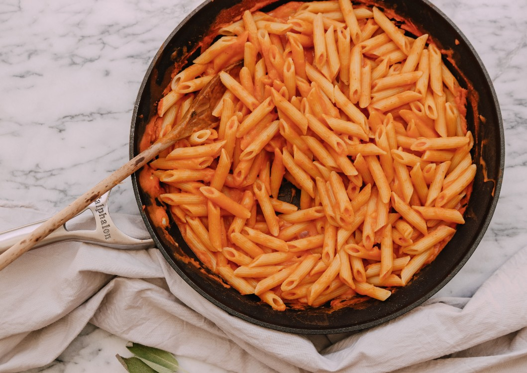 overhead image of a vegan pumpkin sage pasta in a skillet