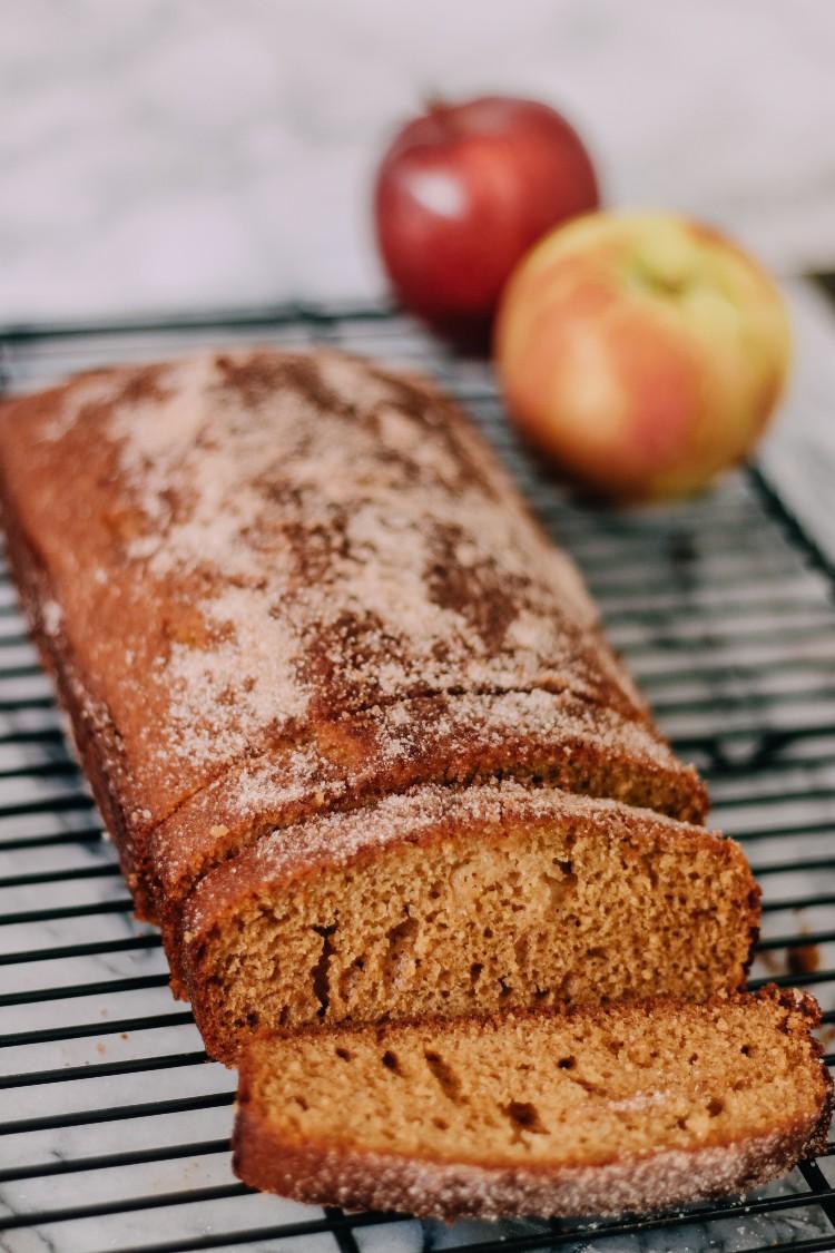 image of sliced apple cider loaf cake on a baking rack