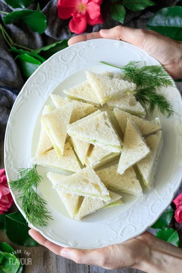 triangular cucumber sandwiches on a white plate