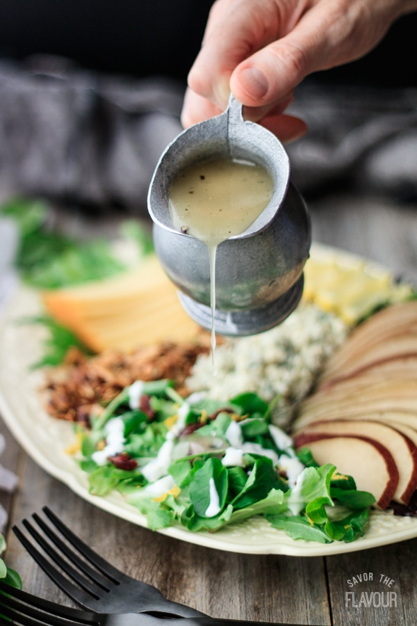 pouring salad dressing over salad