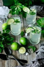 three glasses of lime and mint refresher with fresh limes, black spoons, crushed ice, and greenery