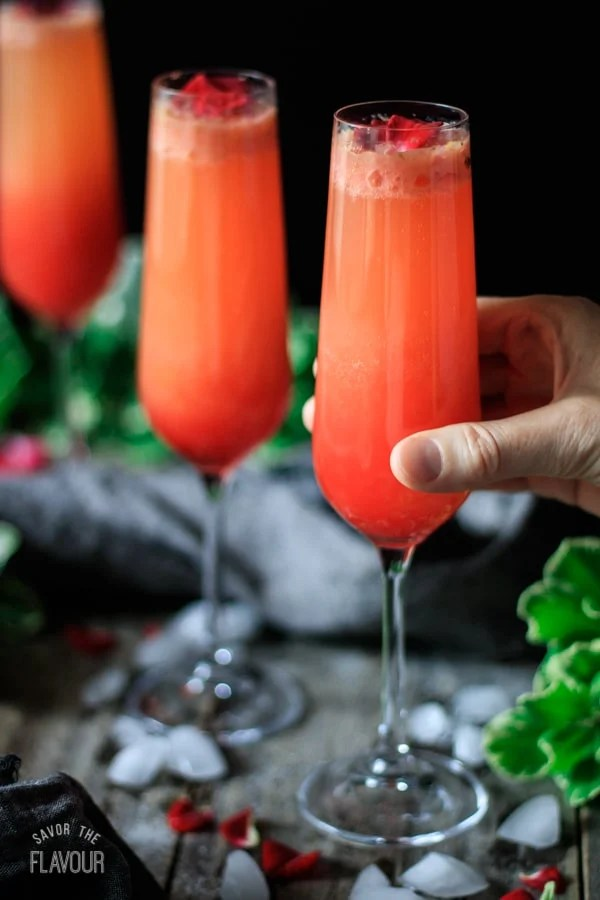 person holding a strawberry citrus blush drink