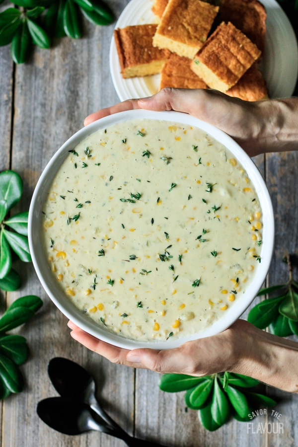 person holding a bowl of corn chowder