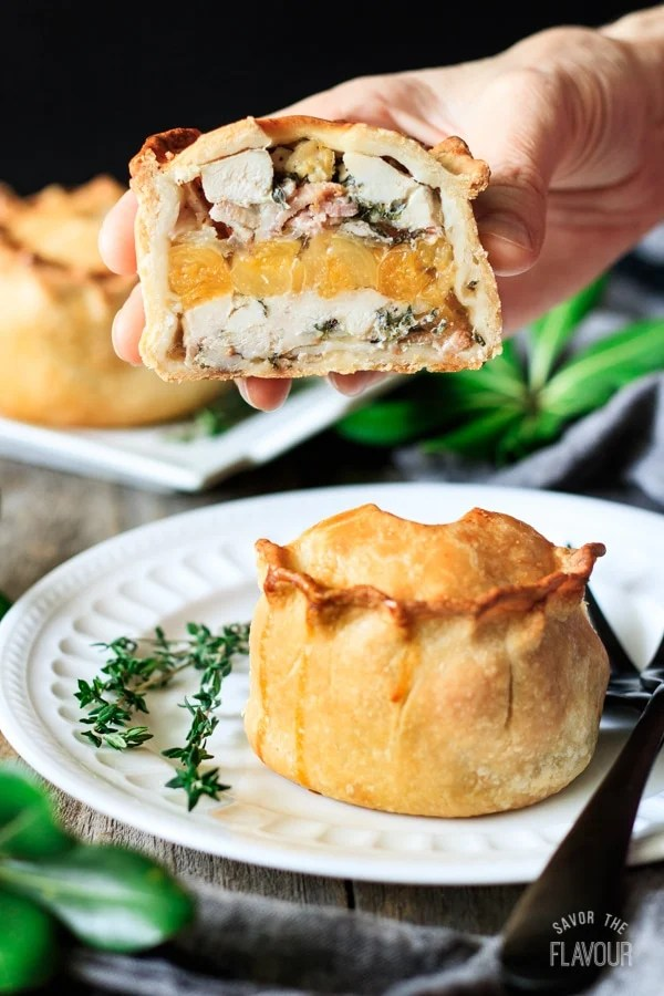 holding a chicken, bacon, and apricot pie cut in half