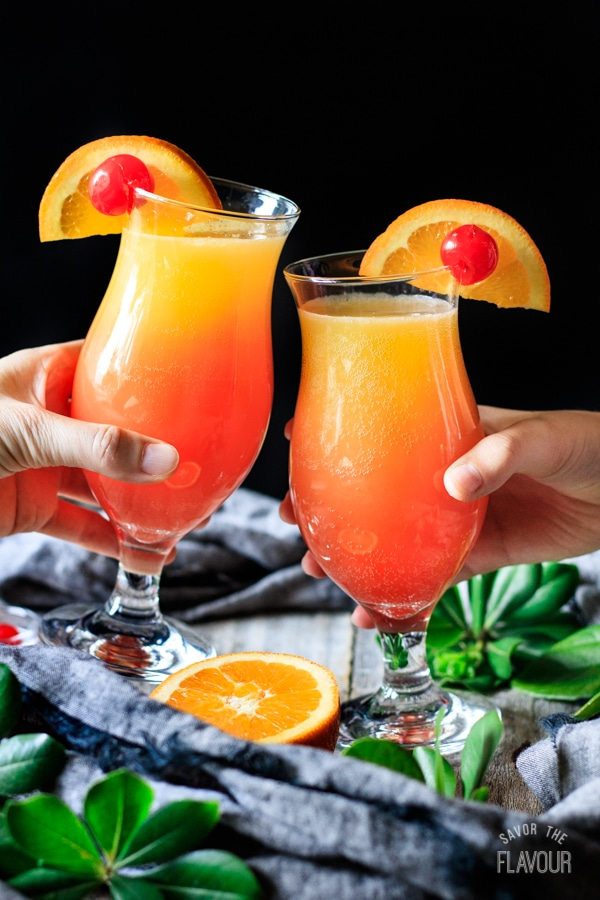 doing a toast with two sweet sunrise drinks