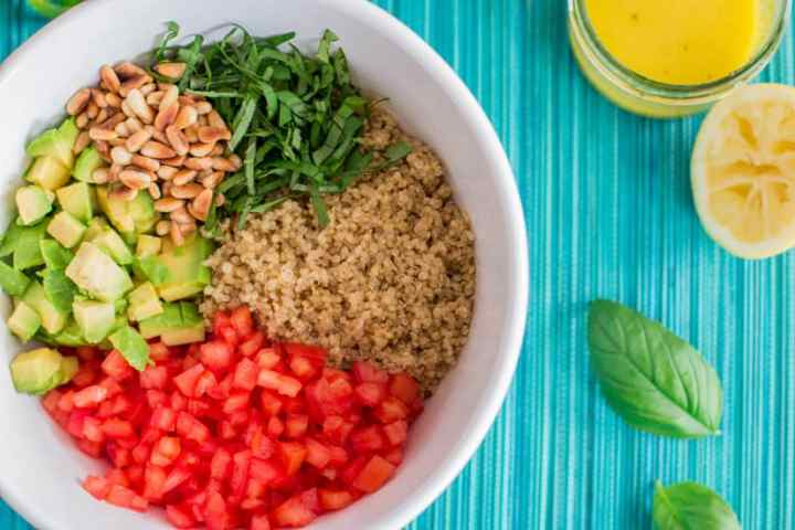 top down view on white bowl with ingredients for quinoa salad