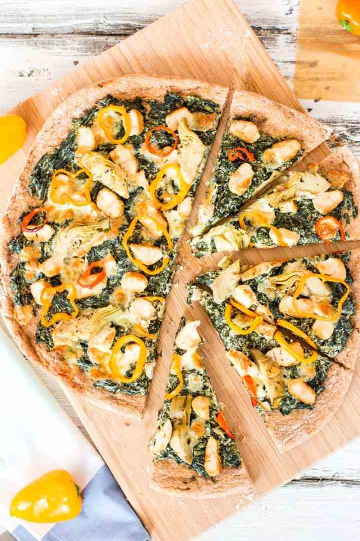 top down view on sliced spinach artichoke chicken pizza