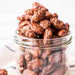 frontal view of jar overflowing with glazed almonds