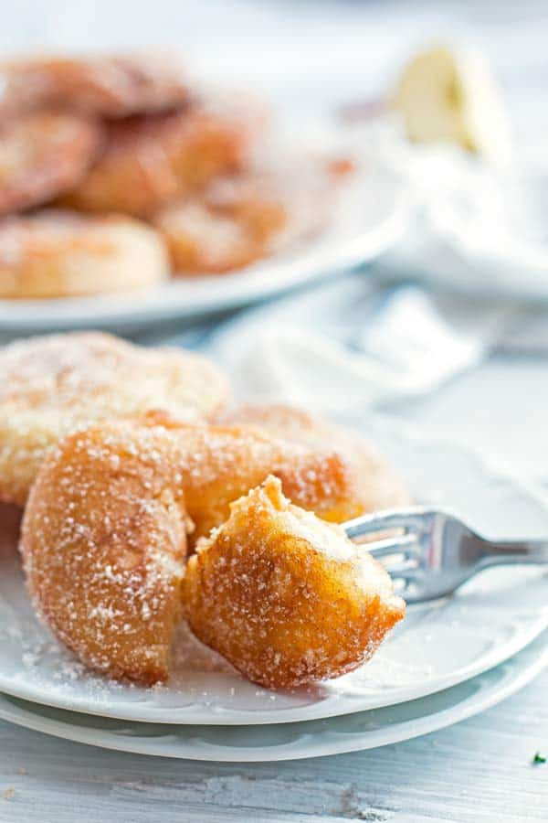 apple fritter on a plate with a fork and a pile of fritters in the background