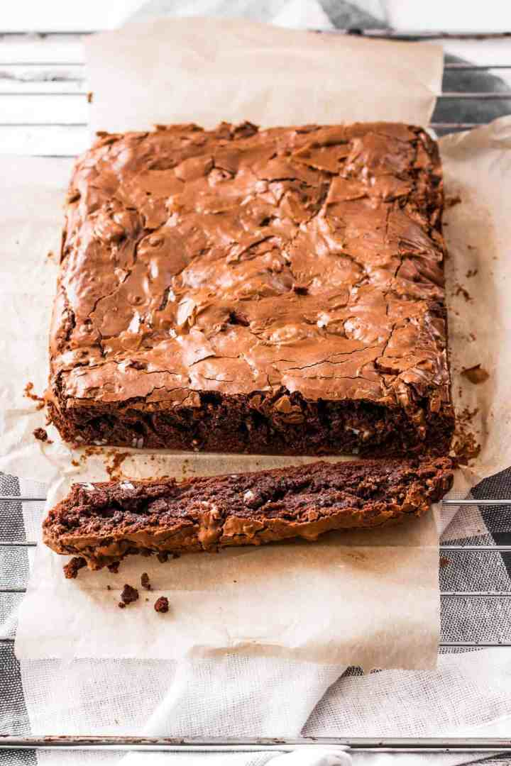 uncut slab of baked brownies on baking parchment