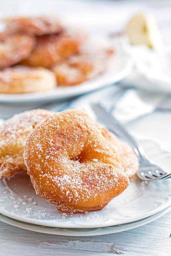 old fashioned apple fritters on a white plate with a fork