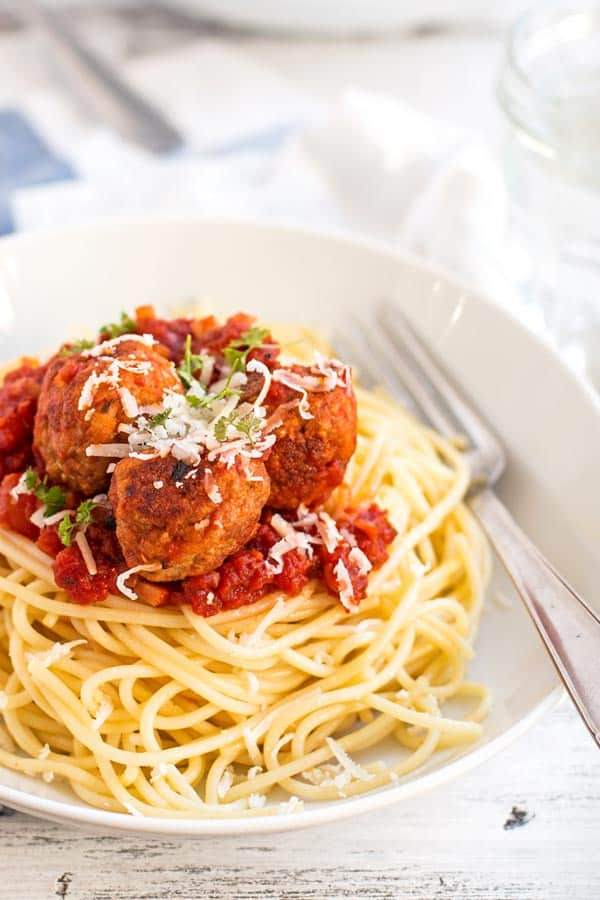 white plate with spaghetti and turkey meatballs in tomato sauce