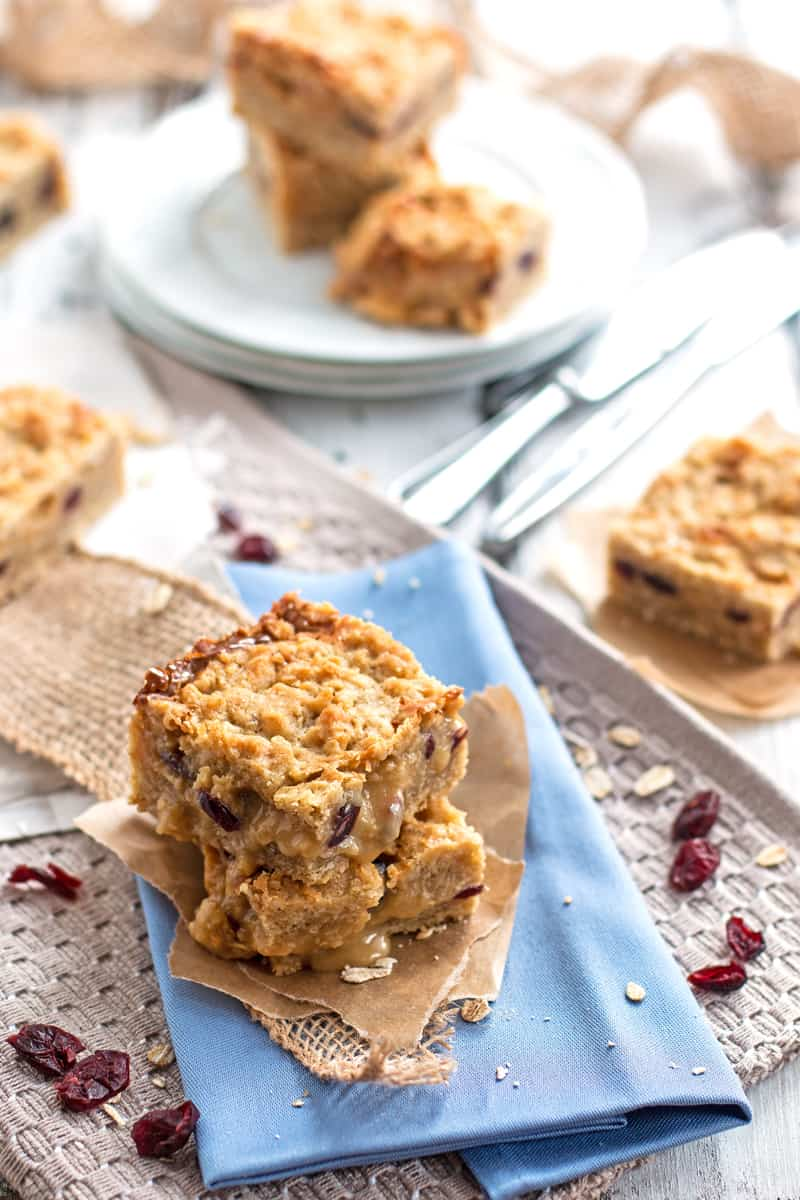 You will love these easy homemade baked Cranberry White Chocolate Fudgy Oatmeal Bars because they are so soft and chewy with a delicious layer of dried cranberries and white chocolate fudge wedged in between! This is the best recipe to add to your holiday baking! Careful: Highly addictive!