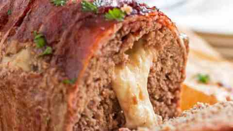 This homemade Mozzarella Stuffed Bacon Wrapped Meatloaf is stuffed with melty cheese and wrapped in plenty of bacon for an easy comforting family dinner.