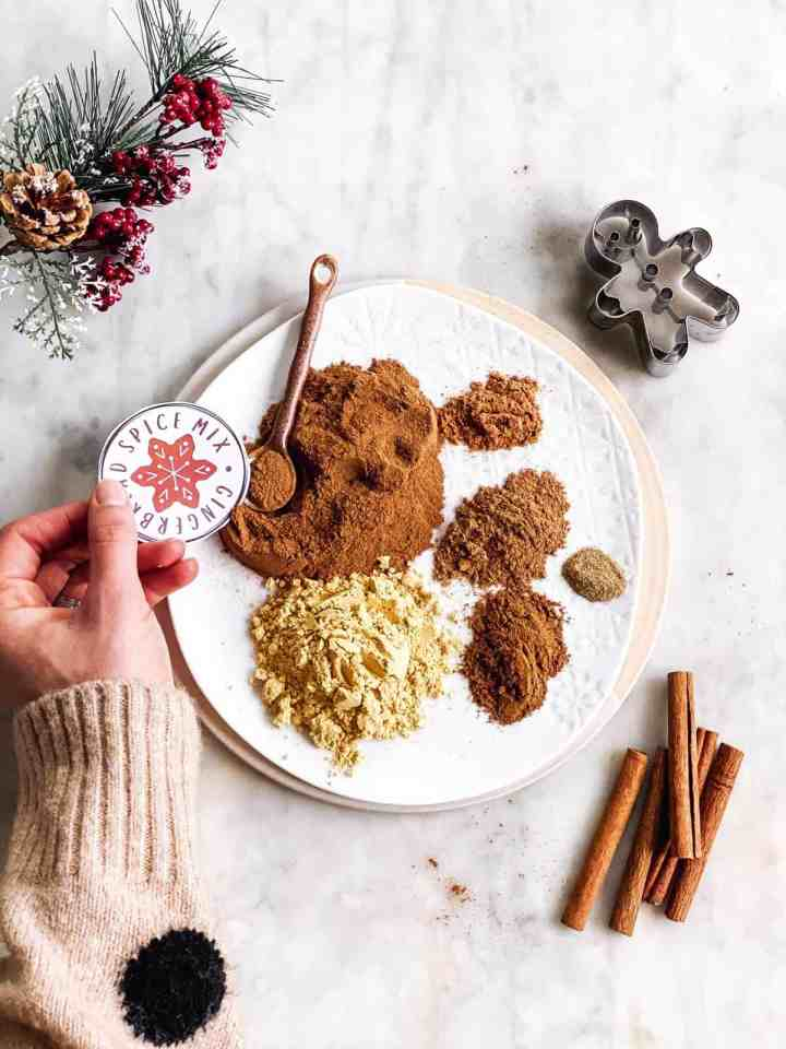 plate with ingredients for gingerbread spice mix with a female hand holding a gift label next to it