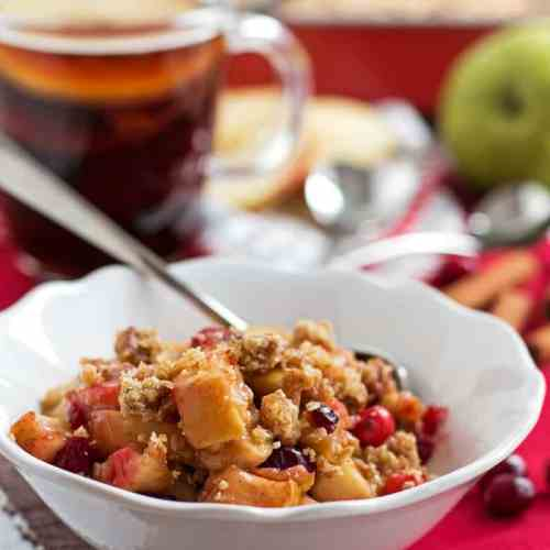 This healthy Holiday Fruit Crisp recipe makes for an awesome festive treat for your family! A simple filling with apples, pears and cranberries topped off with a delicious oat crunch! Less sugar and butter than you'd find in ordinary recipes!