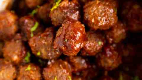 close up photo of sticky bbq meatballs in a white slow cooker
