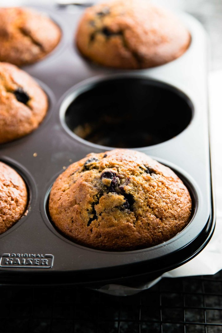 frontal view on muffin pan with baked lemon blueberry muffins