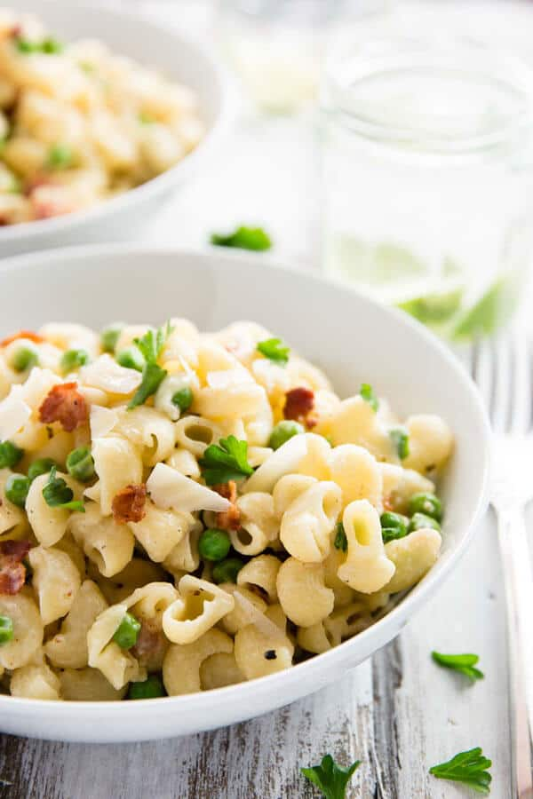white plate with pea and bacon pasta