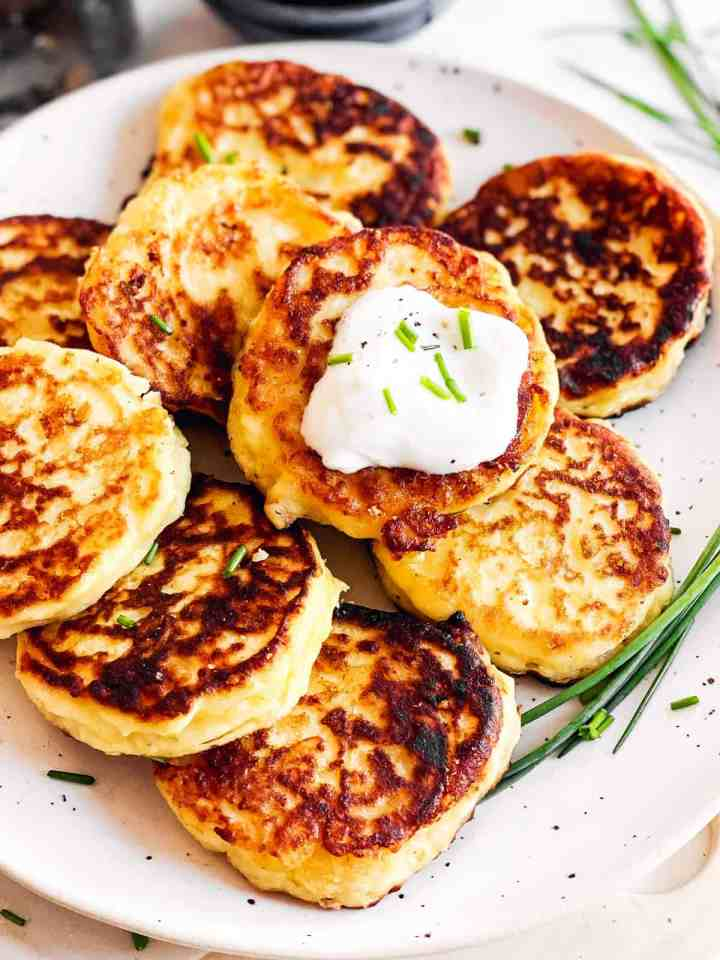 close up view of potato pancakes on white plate with sour cream