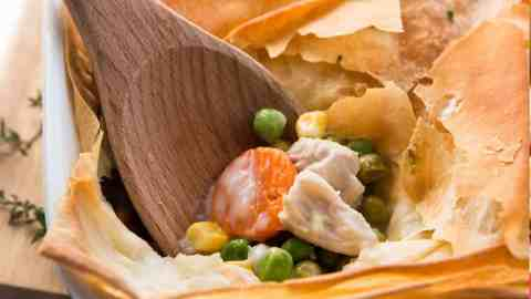 turkey pot pie in white casserole dish with wooden spoon sticking in filling