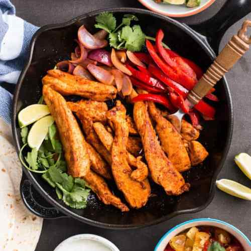 Make these easy chicken fajitas your new go-to weeknight dinner! They cook up quickly in a skillet & everyone can serve themselves their favorite toppings.