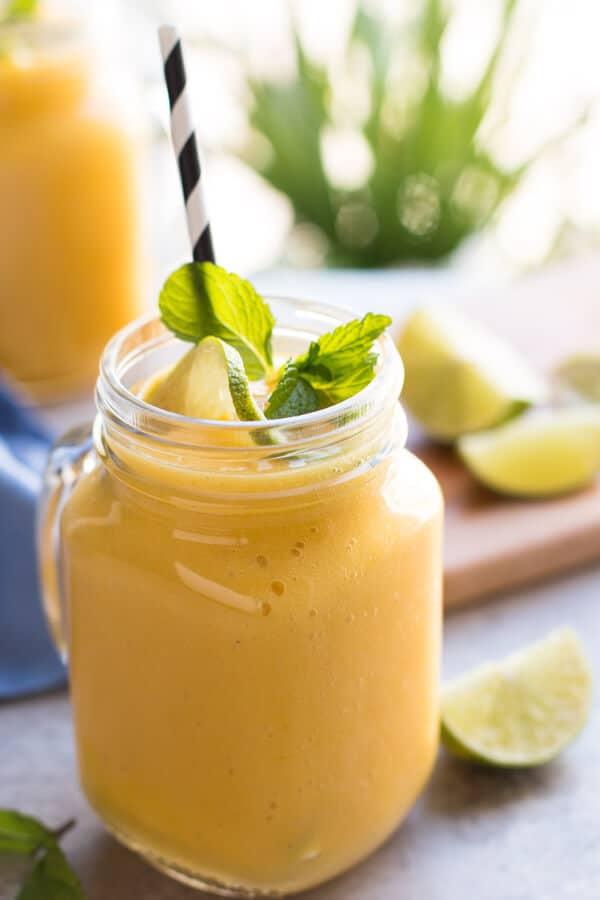 banana mango smoothie in mason jar with straw