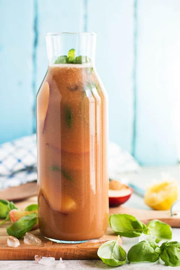 Basil Peach Agua Fresca in a large jug.