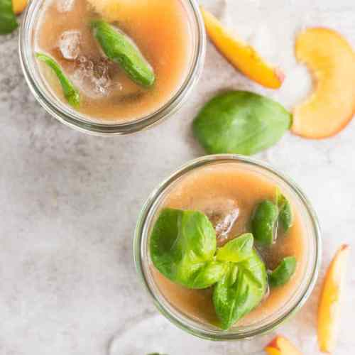Two glasses filled with Basil Peach Agua Fresca.