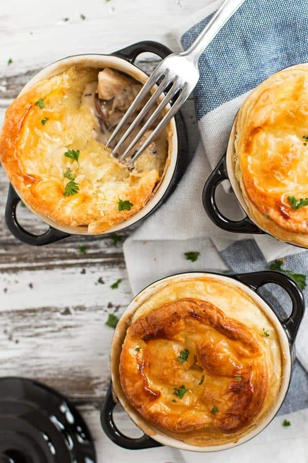 Three individual chicken mushroom pot pies on a dining table.