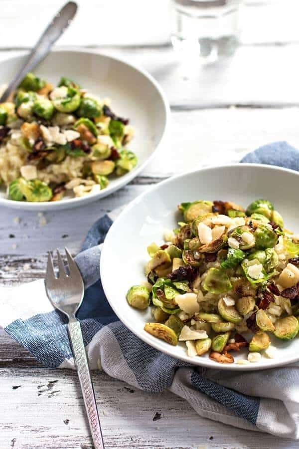 Two plates filled with risotto with bacon and brussels sprouts.