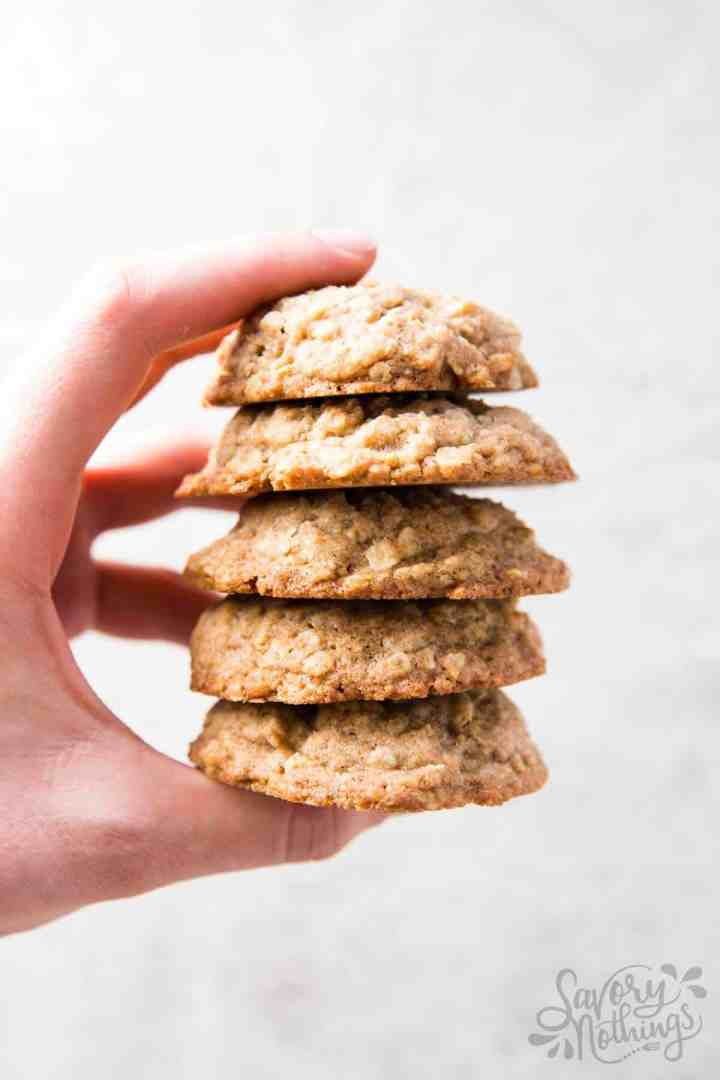 female hand holding a stack of homemade oatmeal cookies