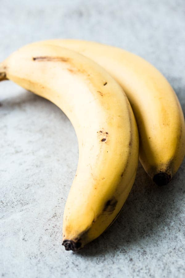 two bananas on light surface