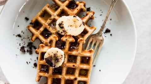 overhead view on female hands holding white plate with banana waffles