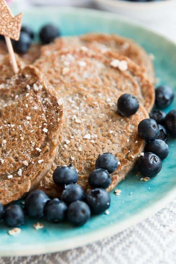 close up of healthy pancakes with blueberries on blue plate