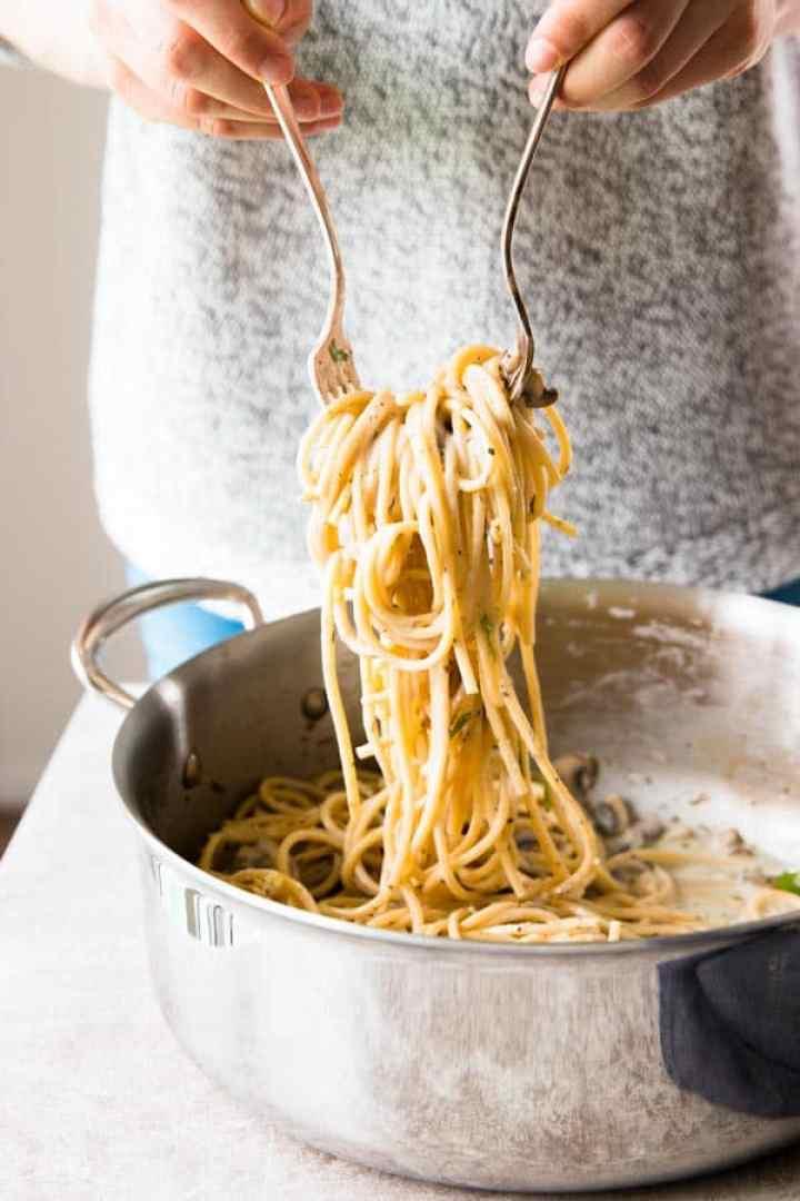 woman in grey shirt lifting mushroom pasta out of pan