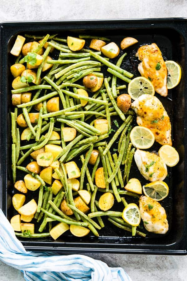 This baked honey garlic chicken is made with potatoes and green beans on a single sheet pan. Try it tonight for an easy weeknight dinner!