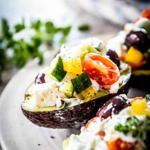 Chopped greek salad stuffed avocados are the perfect summer treat. Make them with tzatziki sauce!