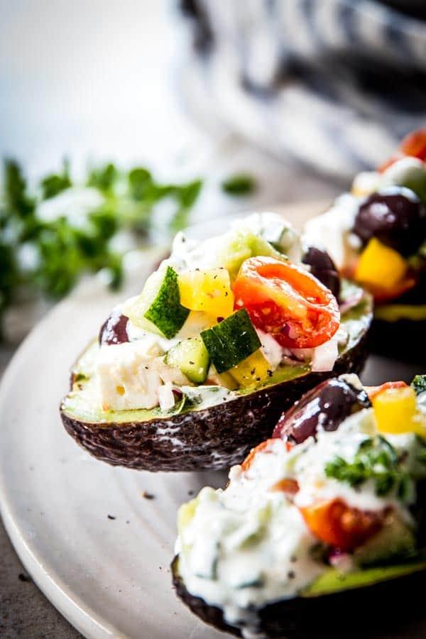 greek salad stuffed avocado on ceramic platter
