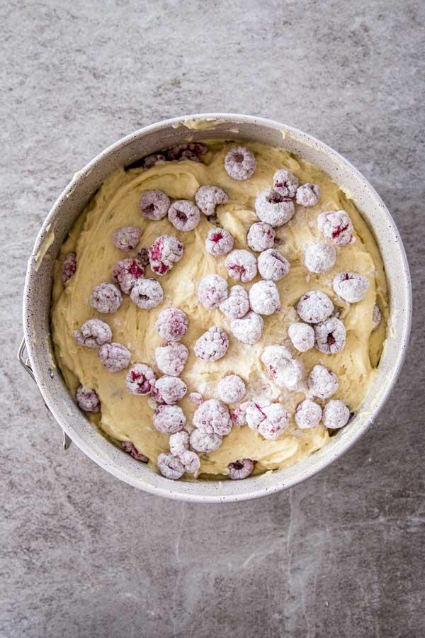 Layering batter and berries for yogurt raspberry cake.