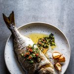 Baked whole fish, stuffed with lemon, rosemary and herbed garlic butter. It's a delicious dinner you can make in 30 minutes tonight!