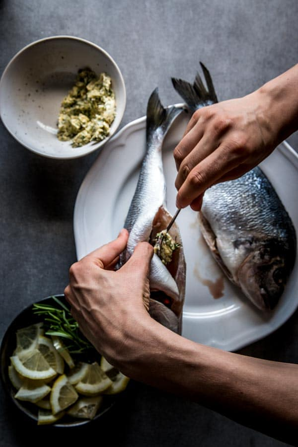 Stuffing baked whole fish with garlic herb compound butter.