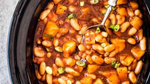 Crock pot baked beans are a fun dish to add to any potluck or party! These are made with BBQ sauce and pineapple - try them this weekend!