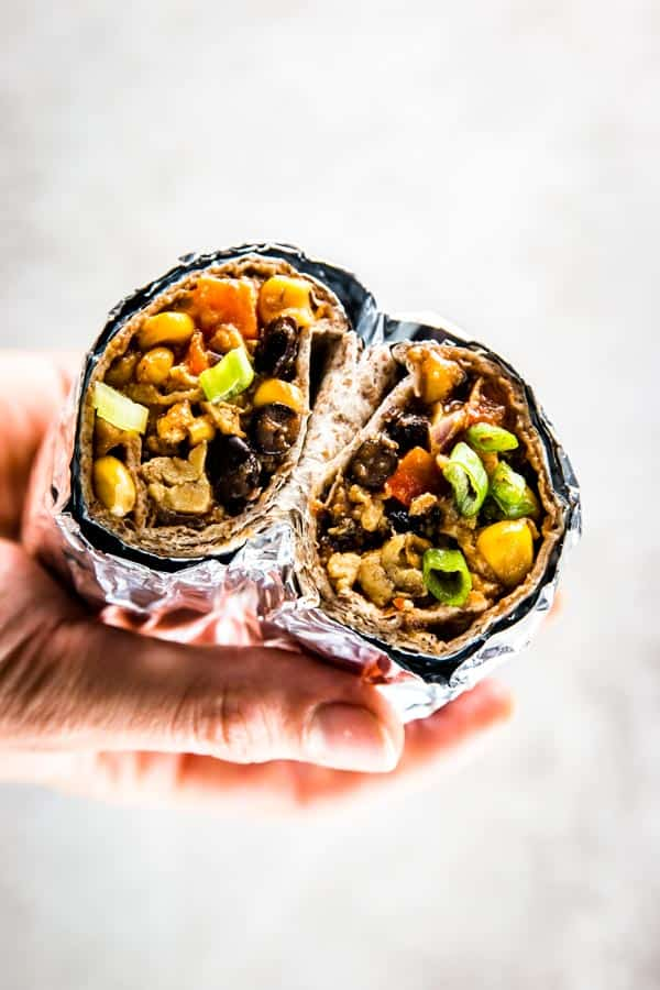 female hand holding breakfast burrito cut in half