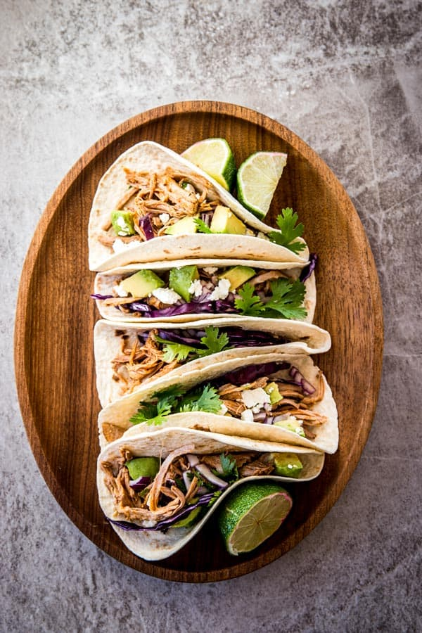 overhead view on pork tacos on wooden platter