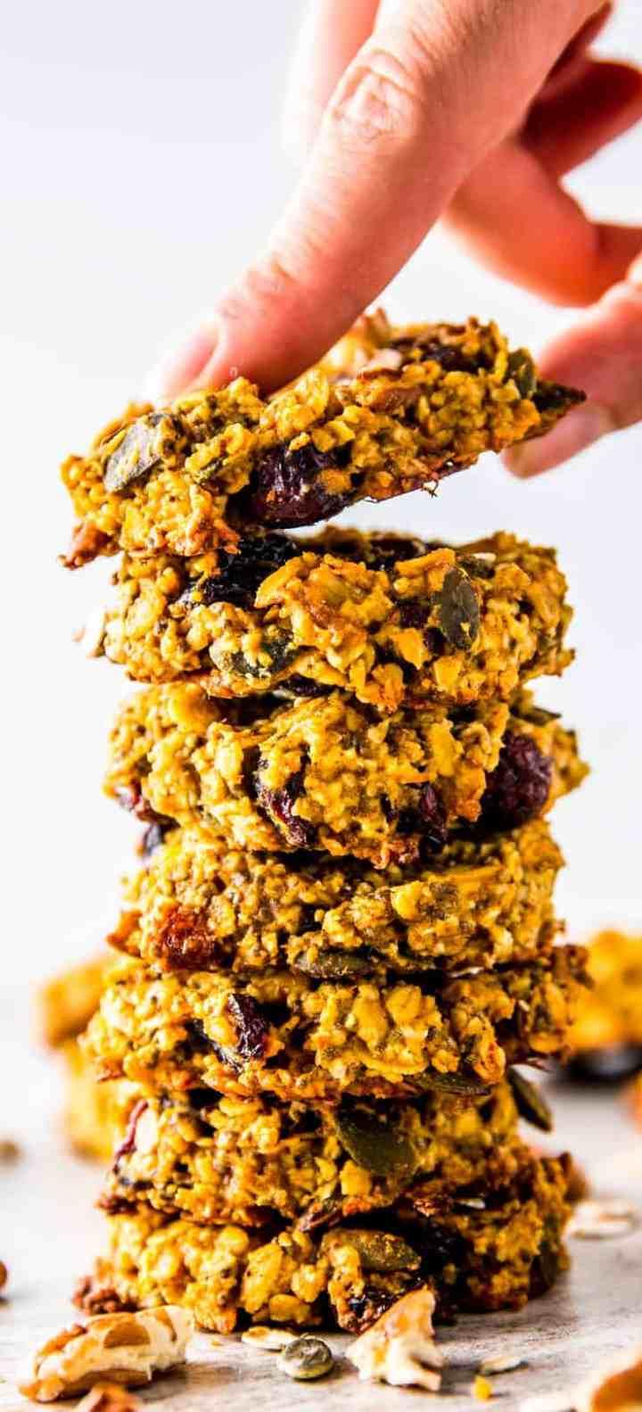 female hand grabbing top cookie from stack of pumpkin breakfast cookies