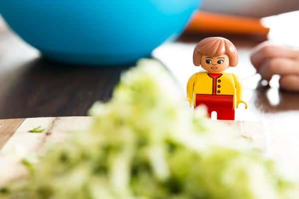 Lego woman standing behind shredded zucchini.
