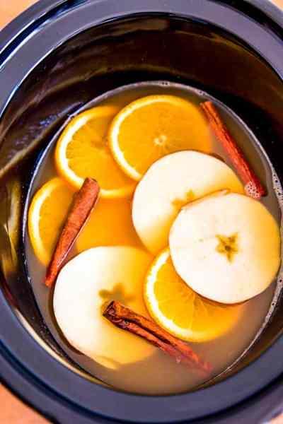 crockpot filled with apple cider, orange slices, apple slices and cinnamon sticks